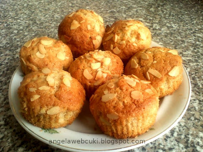 Narancsos tejszínes muffin, kandírozott cukrozott narancshéjas tésztával, valamint mandulaforgáccsal a tetején.