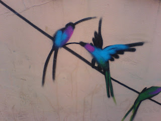 graffiti of 2 blue and purple birds on a wire
