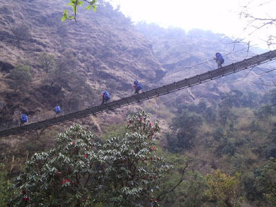 Porters crossing a suspension bridge near Syabru