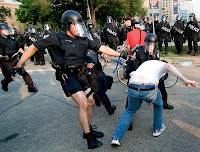 2 police officers in riot gear attack a single protester while a group of officers stand in the background also wearing riot gear