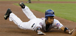 Endy Chavez slides into third after his RBI triple in the first inning
