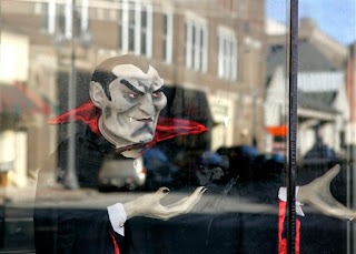 Buildings of downtown Oil City, Pa. are reflected in the windows of a Haunted House with a Dracula replica setup for the Halloween season