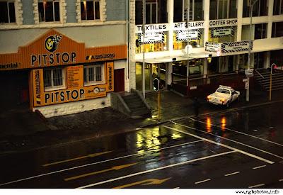 Fotografia di strada di Citta del Capo al mattino, dopo una notte di pioggia, con i riflessi delle luci e dei semafori nelle pozzanghere e sull'asfalto bagnato