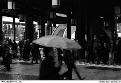 Fotografia in bianco e nero di donna con ombrello a passeggio per le vie di Milano. Macchina fotografica Canon EOS 50 e, ottica Sigma 70-300 f/4-5.6 apocromatica, pellicola Kodak TMax 3200