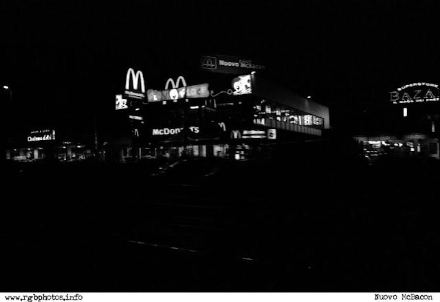 Fotografia notturna di un centro commerciale con le insegne del McDonald's.Macchina fotografica Canon EOS 50e, ottica Sigma 70-300mm f/4-5.6 APO, pellicola Kodak TMax 3200.