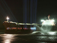 Greenpeace action: projecting solar message onto coal transport ship
