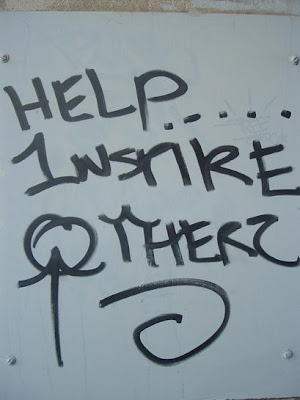the words Help Inspire Others as graffiti on wall