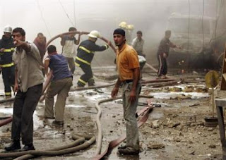 Residents and firemen gather at the scene of a car bomb attack in Baghdad, April 18, 2007. (REUTERS/Ali Jasim)