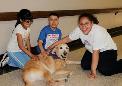 Youth participants in a GDB Lifestyles Workshop, happily petting a yellow Lab