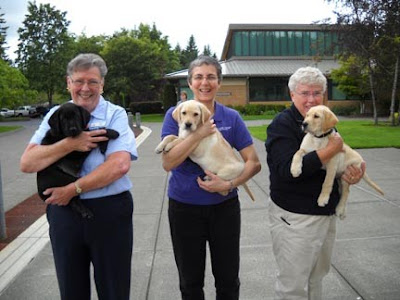 Volunteers holding the puppies that would be presented to their new raisers at an Oregon graduation ceremony