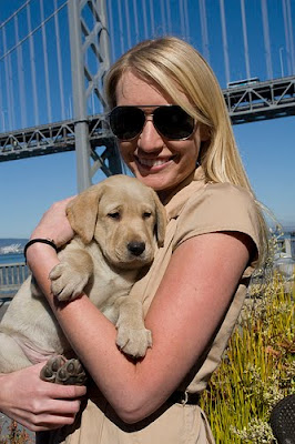 Molly Mahoney holding a yellow Lab puppy