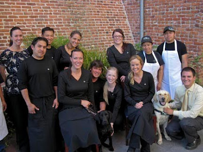 The Melting Pot staff pose with a couple of GDB puppies in training