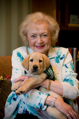 Betty White holding a Guide Dog puppy