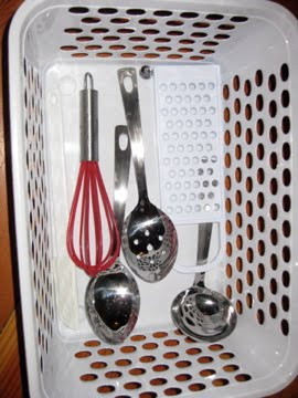 Basket of child-size utensils kept in the kitchen for a child to help prepare dinner. (Photo from The Montessori Child at Home)