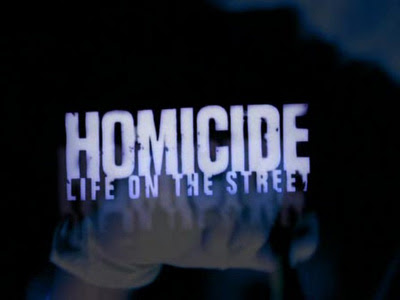 Because this post is about the declining years of Homicide, this shot is taken from the opening titles from those later years. The awesome original titles for Homicide were created by Arlington Road director Mark Pellington. The shot of a barking dog behind a chain-link fence brilliantly established the inner-city Balto setting. In season 5, NBC replaced Pellington's titles with a flashier, X-Files-inspired opening by Imaginary Forces. The overproduced titles helped usher in the show's decline.