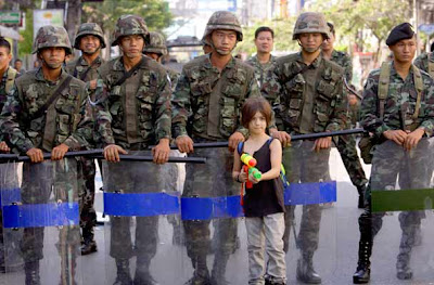 Seven year old boy Apple Rozas, from Britain,  poses with a water gun for his father, in front of Thai soldiers after they cleared an intersection, in Bangkok, Thailand