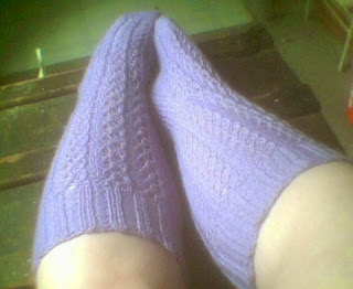 Lilac knee socks on feet to display cabled eyelot pattern