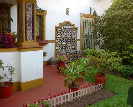 Jardín frontal y fuente estilo Andaluz en una casa en Villa delParque, Buenos Aires