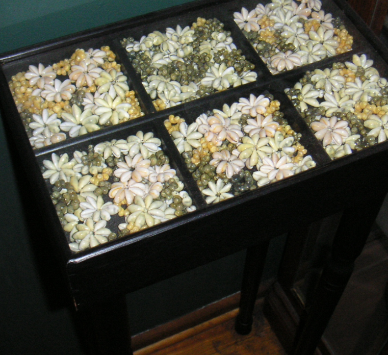a display case made into a table filled with seed lei pieces