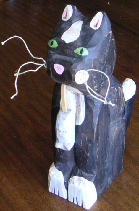 carved cat holding a grey carved mouse