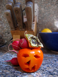 Jack-o-lantern persimmon with radish hair by Rachel Medanic