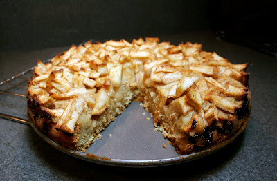 cake topped with chopped apples, with a wedge cut out