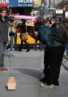 A Tweenbot on a New York City road, being admired by & perhaps assisted by strangers