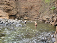 Hawaii vacation volunteers take a break by a swimming hole on the Maui shore.