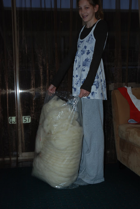 Amelia holding giant bag of new zealand wool for the ginis's