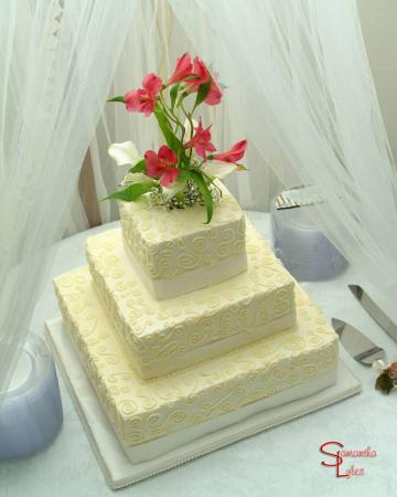 Three tier square wedding cake with swirls and flowers on top