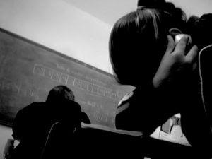 Aluna utilizando o celular escondida em sala de aula