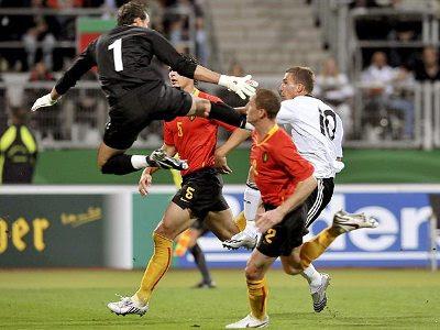 O goleiro Stijnen acerta uma voadora no peito do atacante Podolski