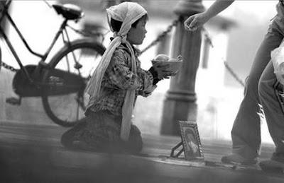 copil sarac cerseste bani pentru mancare