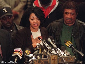 Tawana Brawley addresses supporters at a Brooklyn church in 1997. Her stepfather, Ralph King, is at right.