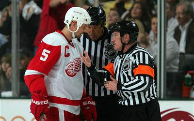 NHL referee Kelly Sutherland #11 explains a no goal call to Nicklas Lidstrom #5 of the Detroit Red Wings against the Dallas Stars during game four of the Western Conference Finals of the 2008 NHL Stanley Cup Playoffs on May 14, 2008