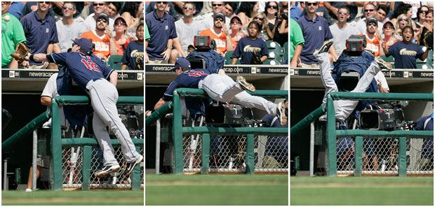 Jayson Nix goes over the dugout rail to catch a foul fly ball hit by Don Kelly