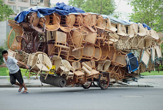 A man pulls a cart loaded with chairs in Shanghai
