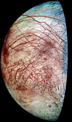 The icy surface of Europa is shown strewn with cracks, ridges and