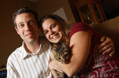 Seth and Kelly Levy hold their 10-month-old cat, Gracie Mae.