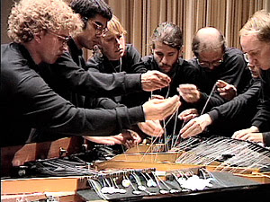 10 musicians armed with fishing line, Popsicle sticks, and plumbing tape to play the bowed piano.