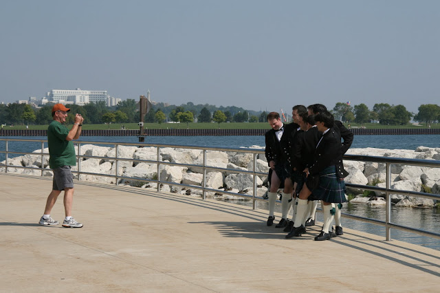 Groomsmen posing for tourist with camera by Calatrava before wedding