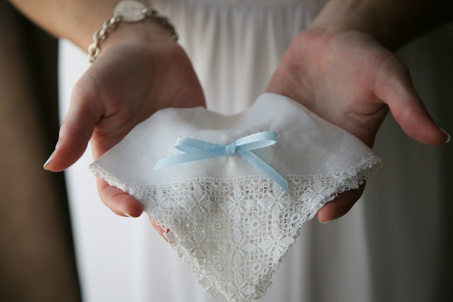 Bride holds handkerchief with blue ribbon on her wedding day