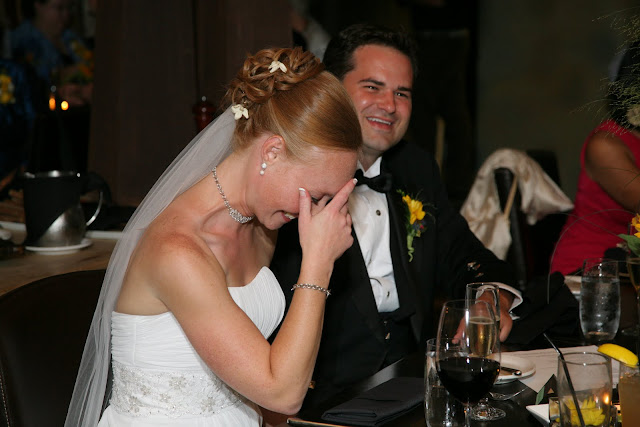 Bride covering face with hand from laughing at toast during Hinterland Erie Street Gastropub wedding reception