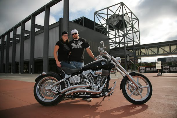 Engagement portrait with couple and motorcycle in front of Harley-Davidson museum