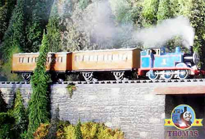 The train Percy and Thomas the tank engine happy puffing along the hillside mountain railway tracks