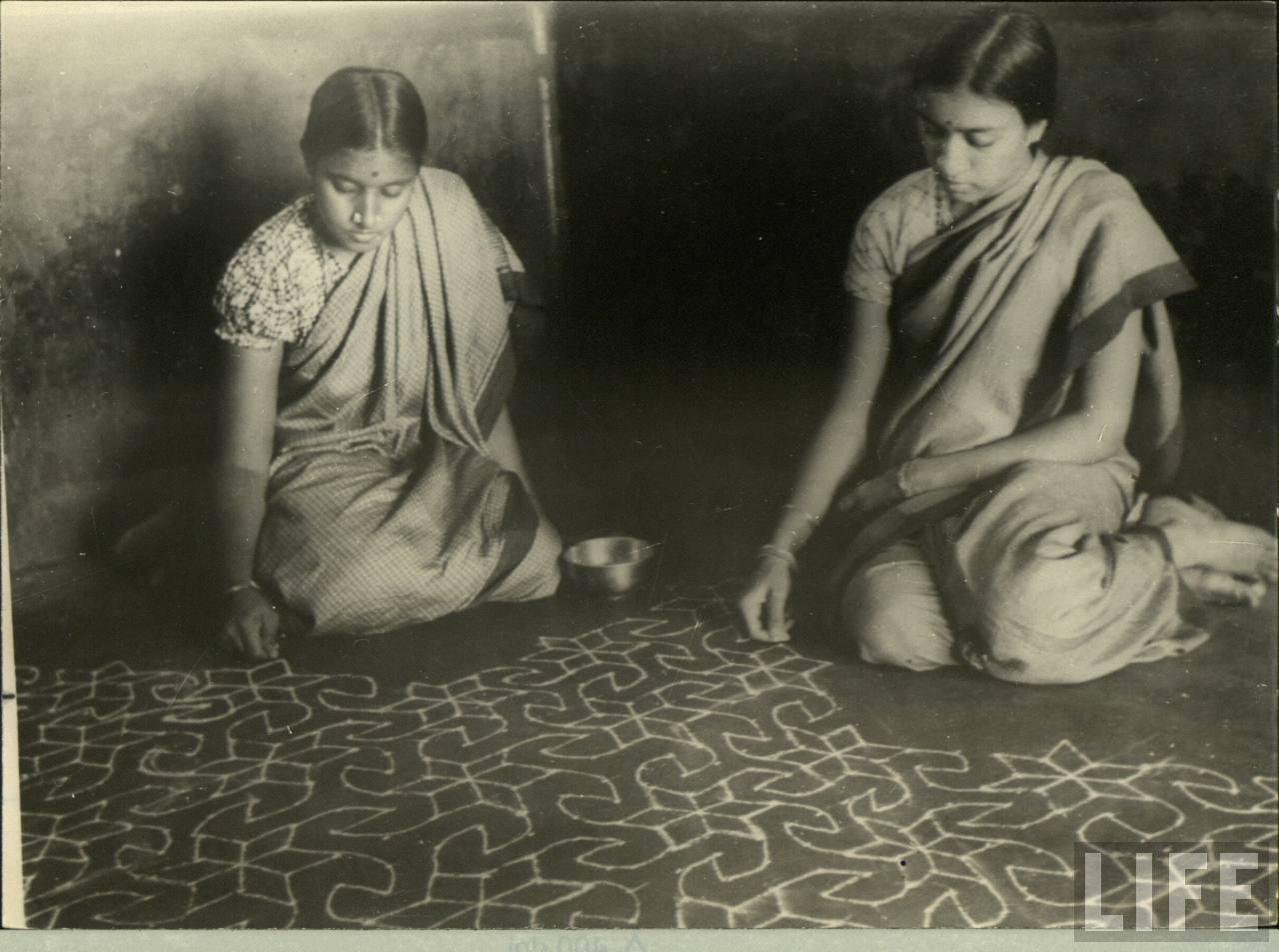 Two ladies creating Alpana (Rangoli) on the floor