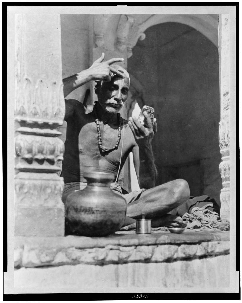 Brahman priest painting his forehead with the red and white marks of his sect and caste - Early 20th Century