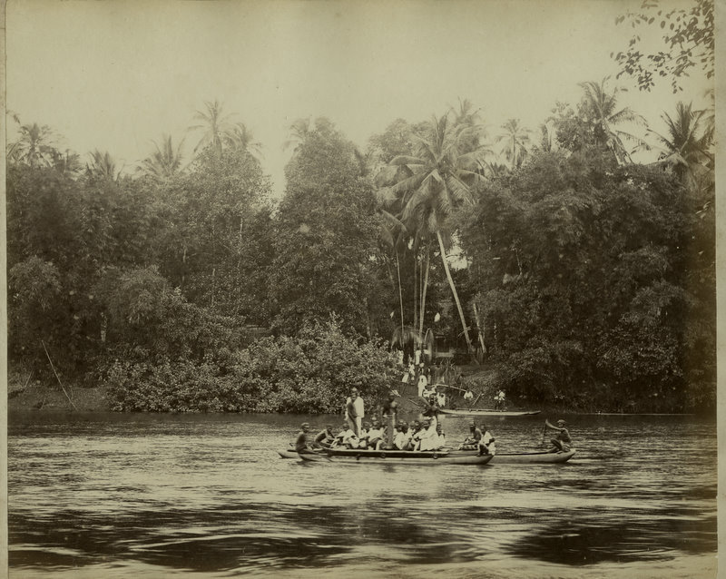 People in Canoes on River