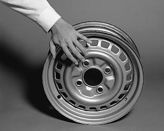a foto 1 mostra parte de um braço de homem com camisa branca de punho e a esquerda mão sobre um aro (roda de automóvel); a 2 é uma fotomontagem na qual aparece uma perna de homem sentado e com a calça suspensa até o joelho de onde sai uma torneira, que aberta, deixa a água cair dentro de um balde de alumínio que está quase cheio; na foto 3 um homem (deduz-se pelas pernas de calças jeans e sapatos masculinos pretos de cadarço) parece andar sobre um caminho pavimentado de ovos de galinha brancos e inteiros; na foto 4 aparecem dois homens (pelas mãos e camisas de punhos brancos: um segura um pato malhado, grande e escuro e outro, um