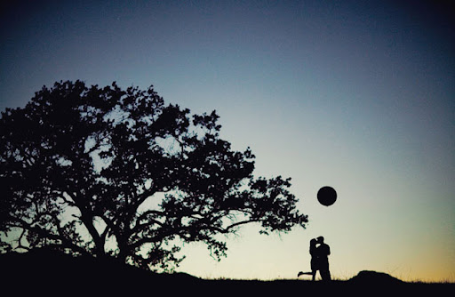 silhouette on hill with balloon couple